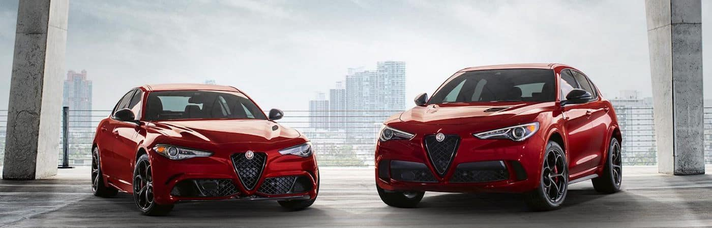 Red Alfa Romeo models parked in front of a cloudy sky