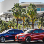 Two Alfa Romeo Stelvio models parked under palm trees to signify a possible electric version of the car.