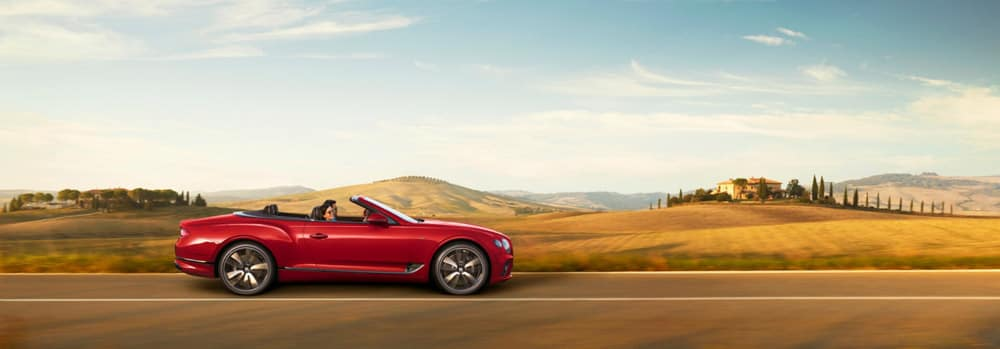 Continental-gt-convertible-driving-past-wooded-hill-italy