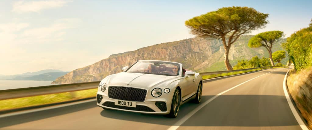 new white Bentley Continental GT Convertible driving by cliffs and sea in Italy