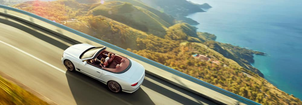 new-white-Bentley-Continental-GT-Convertible-driving-on-high-mountain-road-with-sea-to-the-right