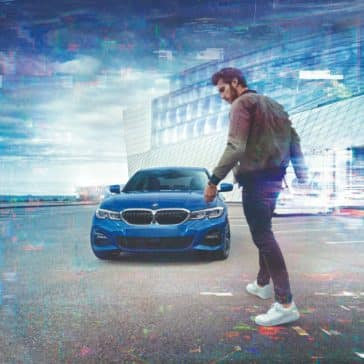 Frontal view of the BMW 3 Series with a man in the foreground.