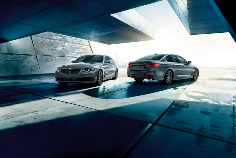 Zoomed out photo depicting two BMW 5 Series, one facing frontwards and one backwards.