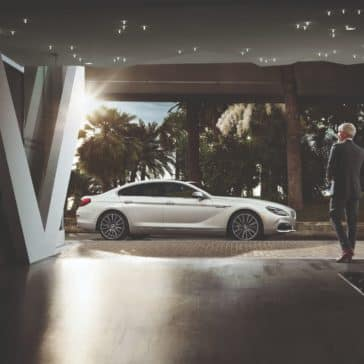 Zoomed out photo of the BMW 6 Series with a man alongside.
