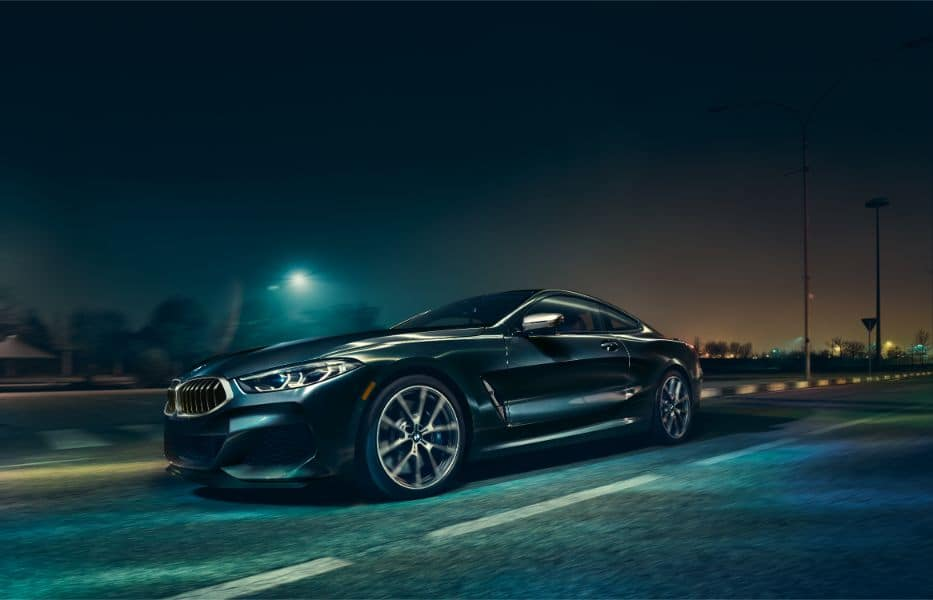 Exterior shot of the 2019 BMW 8 Series driving, showing the front wheel and side profile of the vehicle.