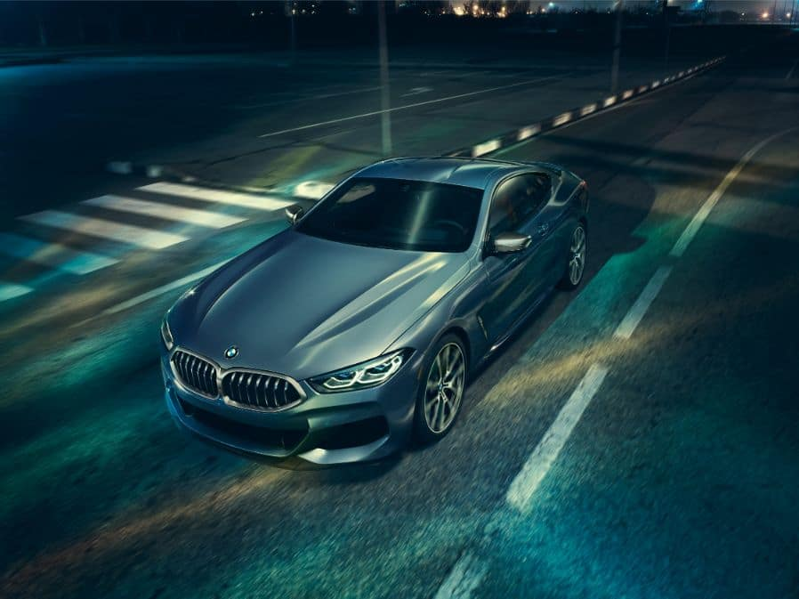 Aerial photograph of the 2019 BMW 8 Series driving along a road at night, showing the hood, windshield and headlights.
