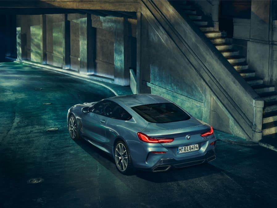 Aerial shot of the 2019 BMW 8 Series driving along a wall, shows the rear profile of the vehicle.