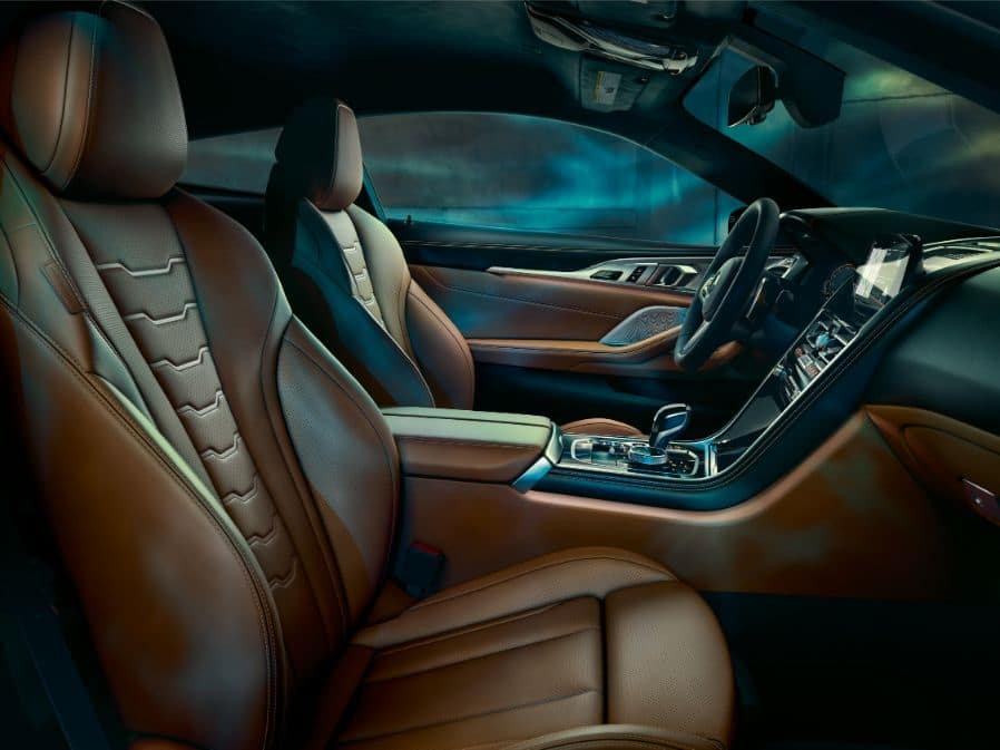 Interior photo depicting the passenger seat, middle console, and driver's seat of the 2019 BMW 8 Series