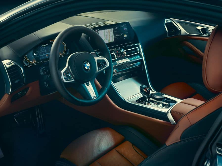 Interior of the 2019 BMW 8 Series, showing the steering wheel, navigation pane, and gearshift.
