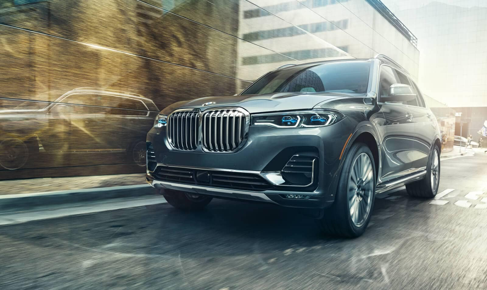 A frontal picture of the 2019 BMW X7 driving along an urban road.
