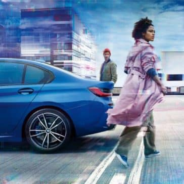 Rear view of the 2019 BMW 3 Series, with a woman in the foreground and a man in the background.