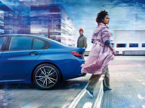 Rear view of the BMW 3 Series, with a woman in the foreground and a man in the background.