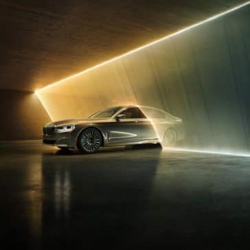 Exterior photo of the BMW 7 Series depicting the car driving halfway through a wall of light.