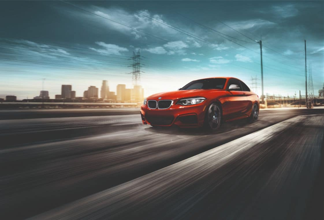 Side view of the BMW 2 Series Coupe driving along a highway.