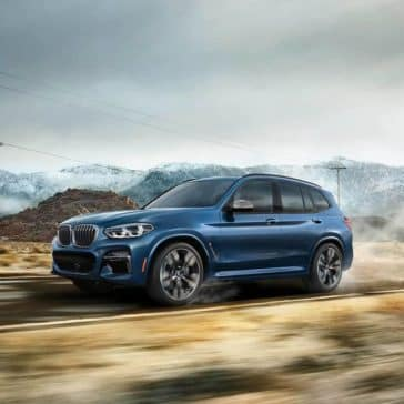 Picture of the 2019 BMW X3 driving along a rural highway.