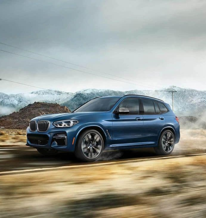 Picture of the BMW X3 driving along a rural highway.