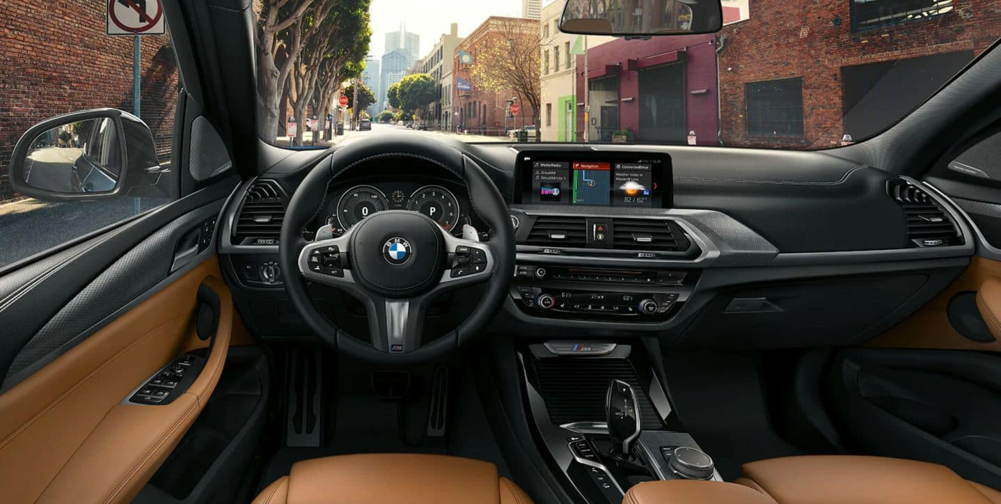Interior of the BMW X3 showing the steering wheel & dashboard.