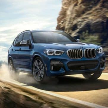 Close-up of the 2019 BMW X3 driving along a rural highway.