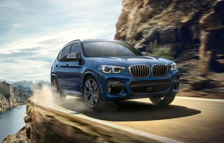 Close-up of the BMW X3 driving along a rural highway.