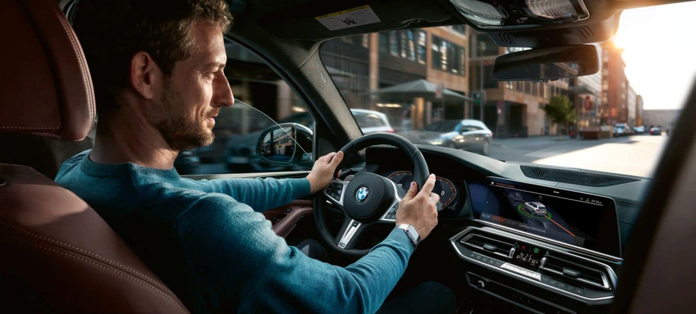 An interior shot of the 2020 BMW X5, showing a man driving in an urban neighborhood.