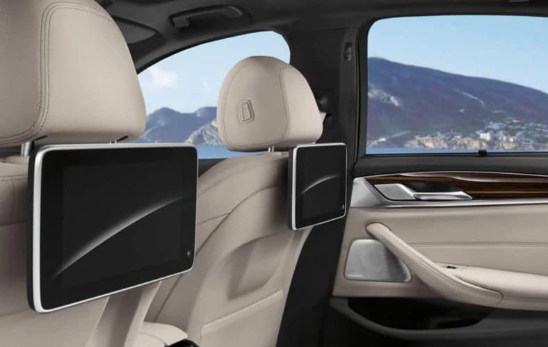 An interior photo showing the optional rear headrest entertainment in the BMW 5 Series.