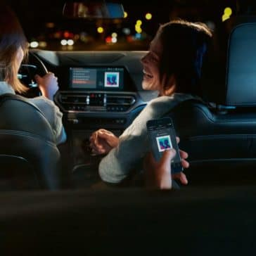 An interior photo of the 2019 BMW 3 Series showing multiple passengers, one using Apple Carplay to play music.