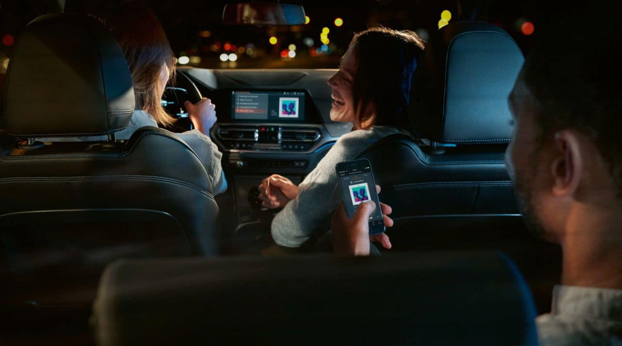 An interior photo of the BMW 3 Series showing multiple passengers, one using Apple Carplay to play music.