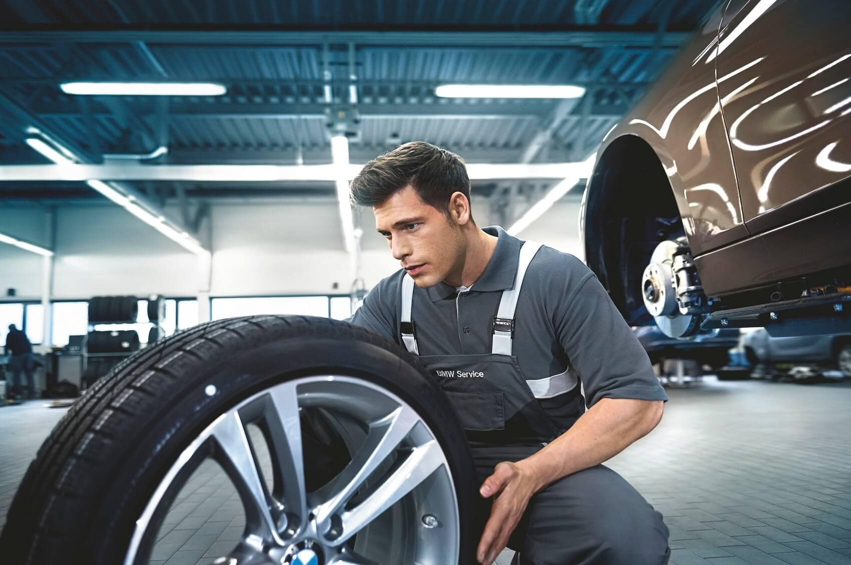 BMW Technician Inspecting Tire at Service Center