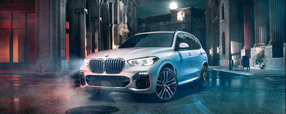 White BMW X5 on a dark city street