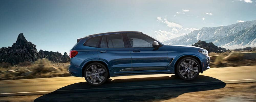 Blue BMW X3 driving on a desert road