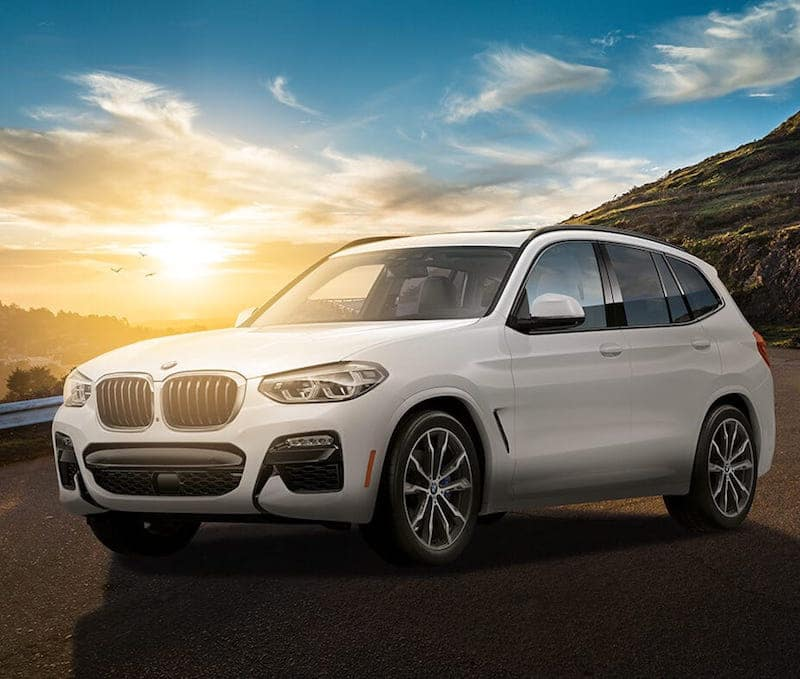 White BMW X3 parked in front of a sunset on a mountain