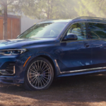 2020 bmw x7 blue exterior parked outside in wooded area