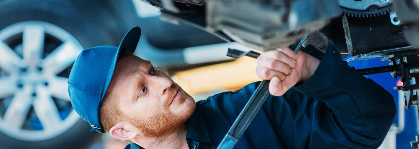 mechanic working under car with large wrench close up