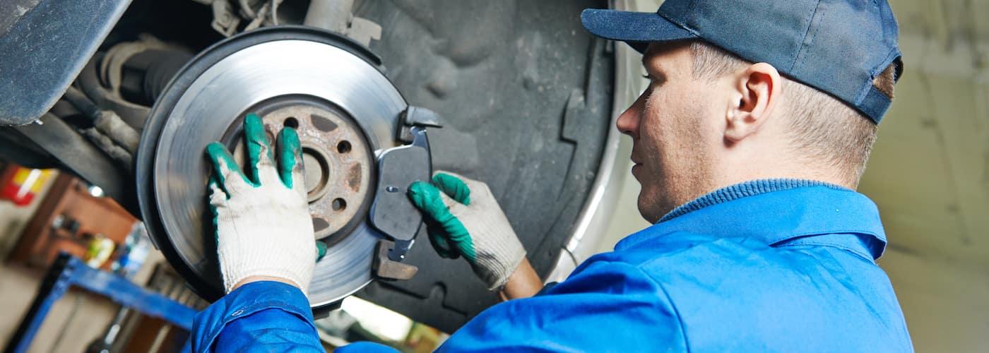 close up of mechanic repairing brakes and suspension