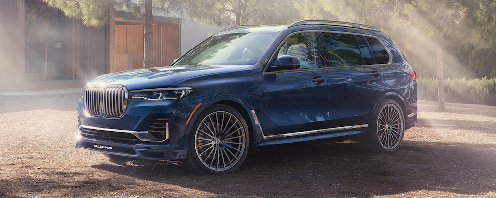 2021 bmw x7 blue exterior parked outside in a misty wooded area
