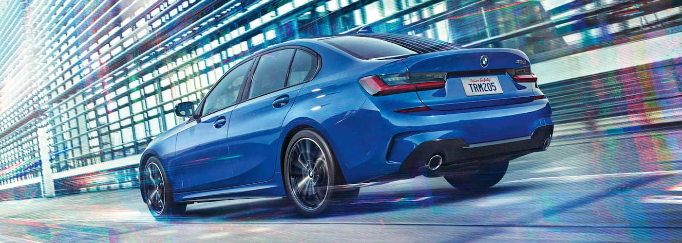 bmw 3 series blue exterior driving down road quickly