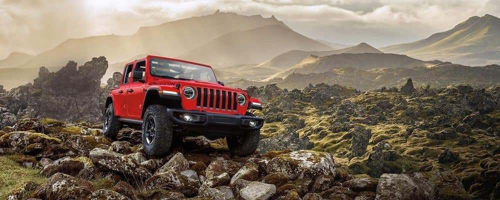 2020 Jeep Wrangler driving over large rocks near a mountain