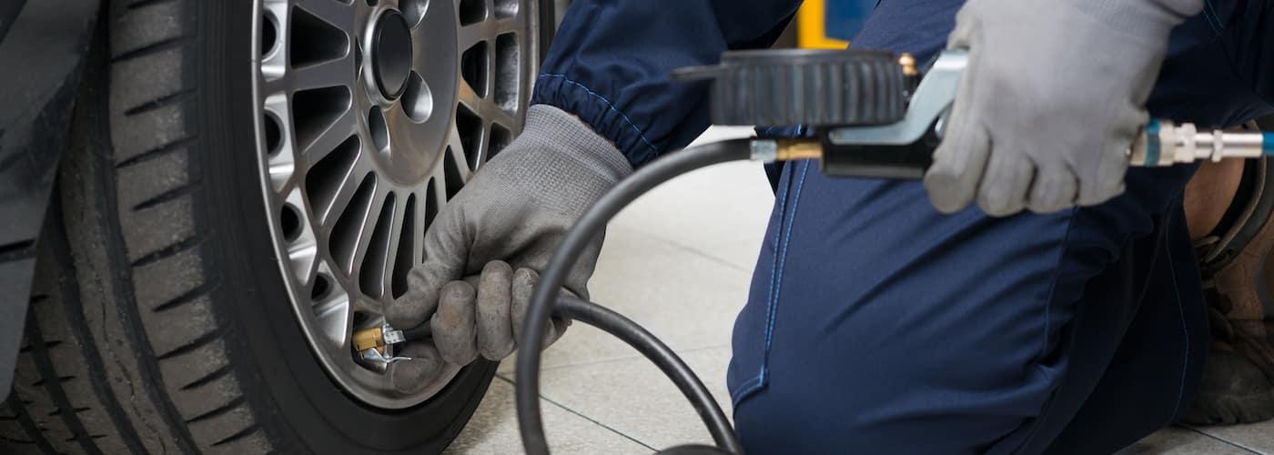 mechanic inflating tire pressure