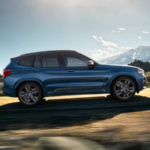 2020 bmw x3 blue exterior driving down scenic road