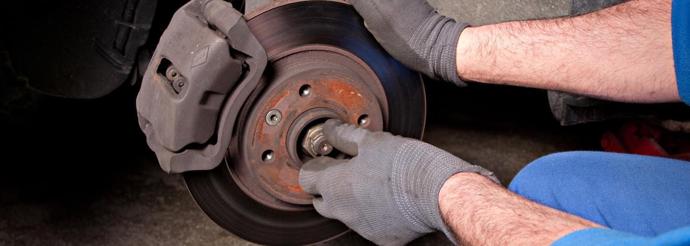 close up of mechanic repairing brakes