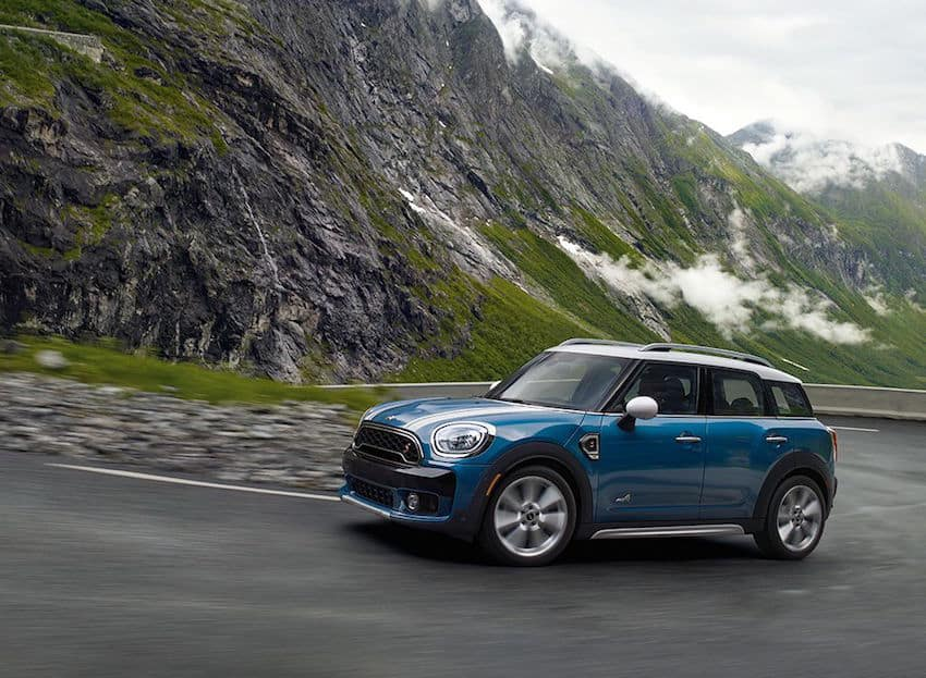Blue MINI Cooper driving in front of a mountain
