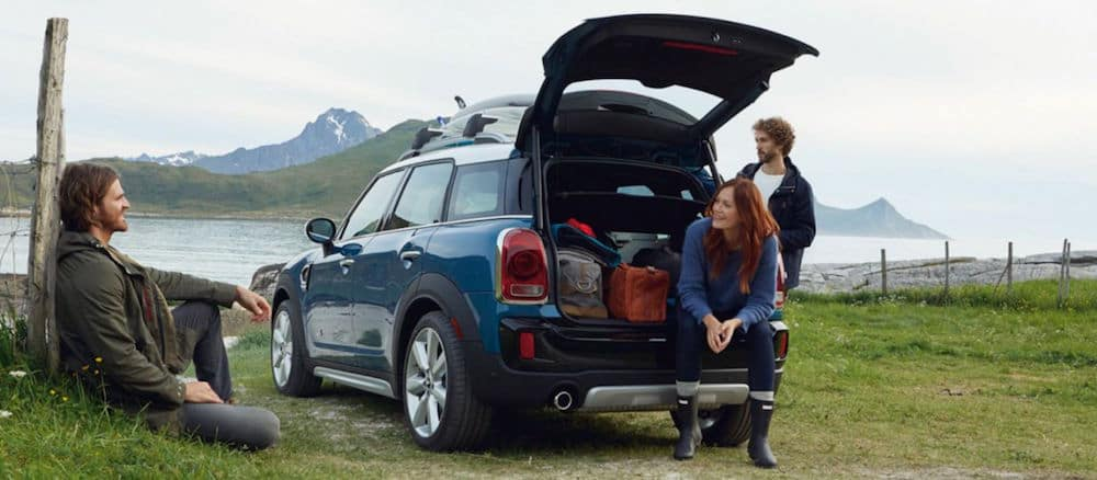 Friends hanging by a blue MINI Countryman with the trunk popped