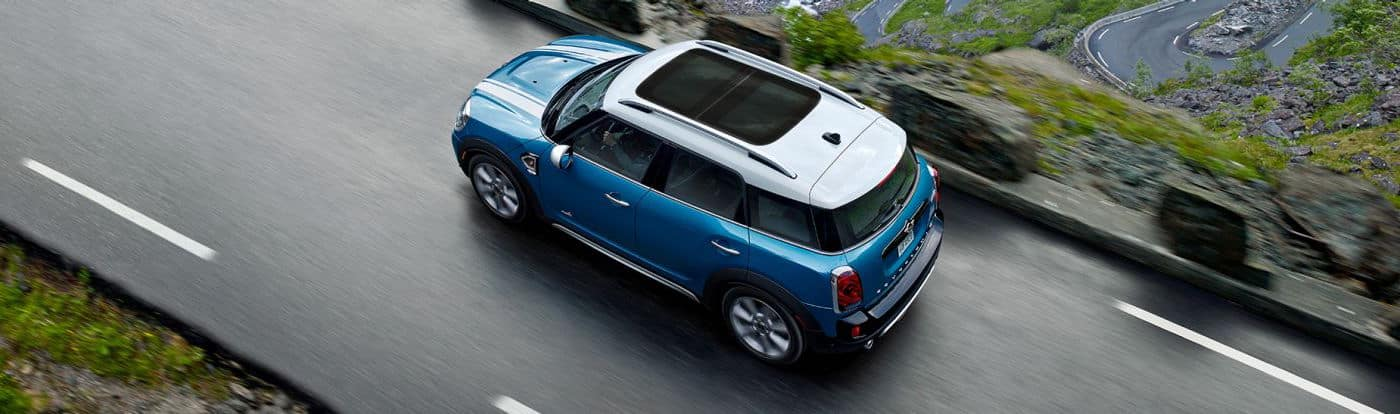 Looking down on a blue MINI driving down a winding road