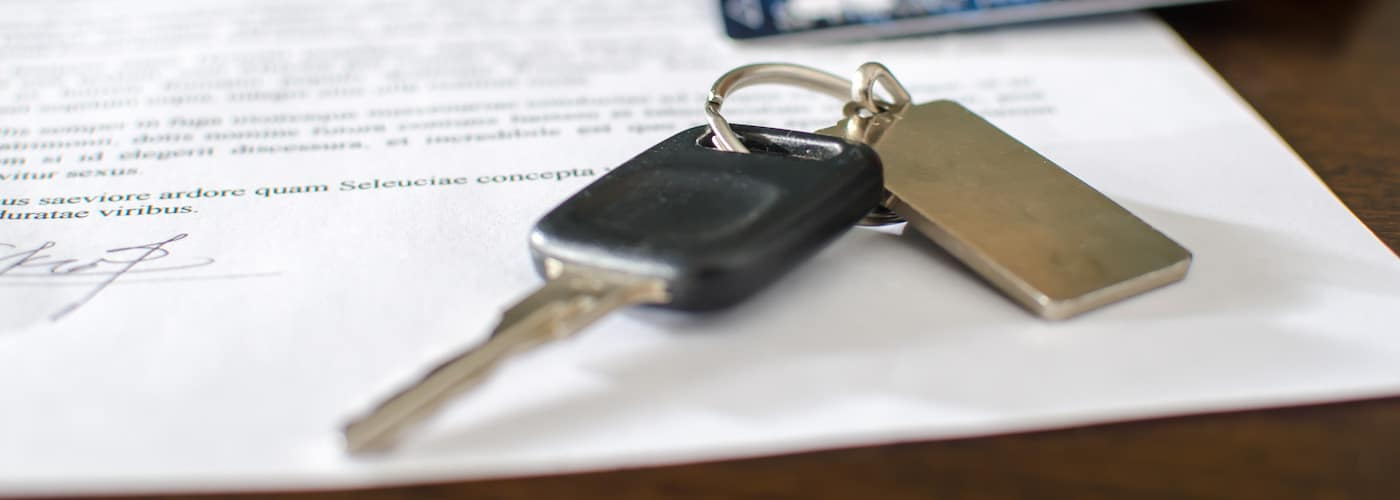 financing papers with car key close up