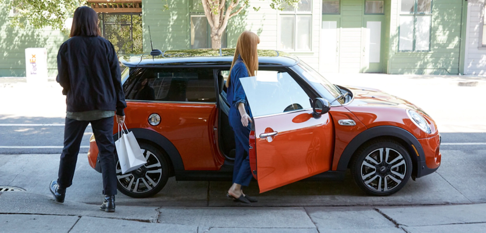 2020 mini cooper red exterior parked outside with two people entering the vehicle