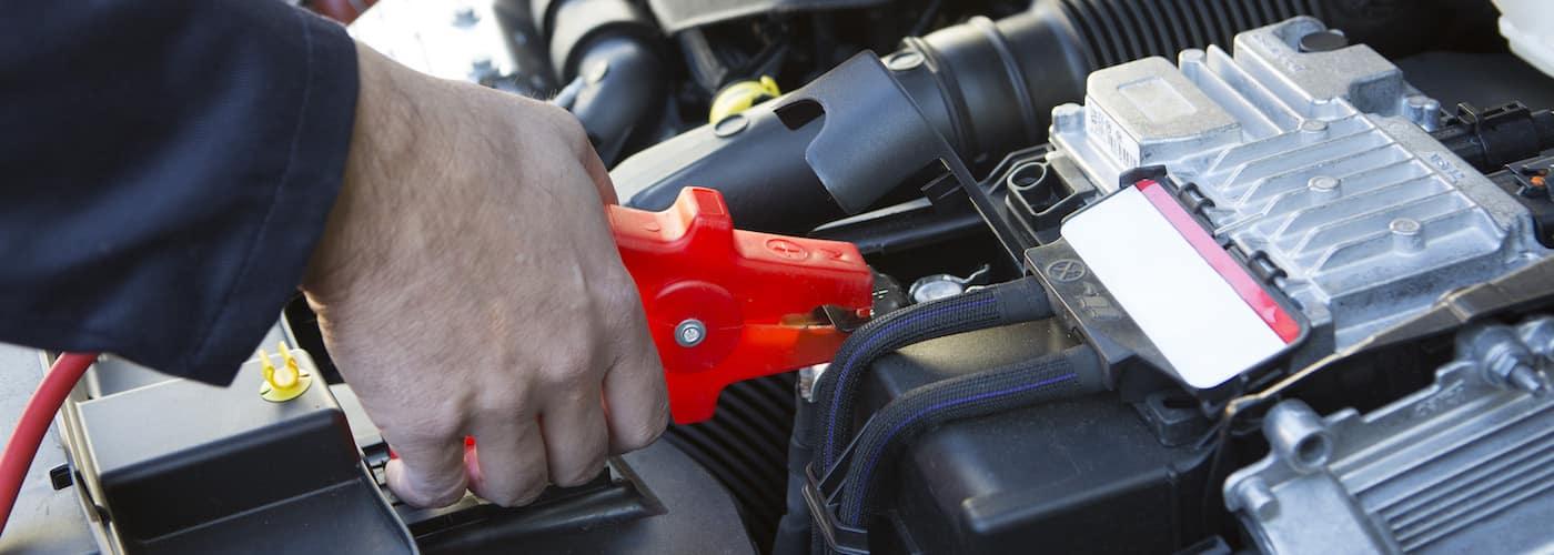 close up of mechanic jump starting car battery