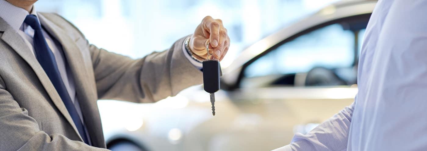 car salesman handing keys over to buyer