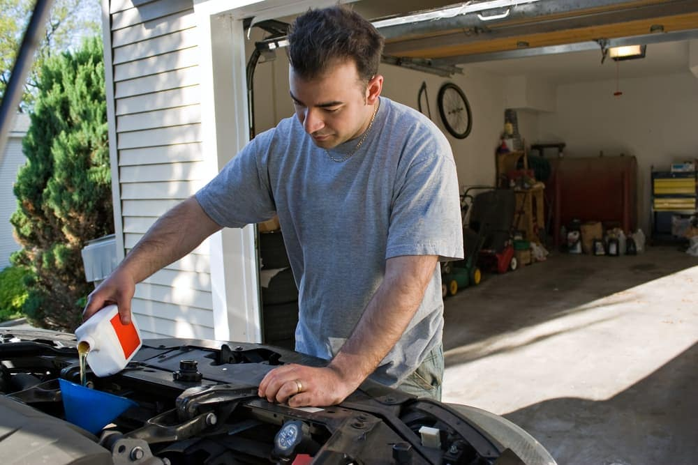 man changing oil in car