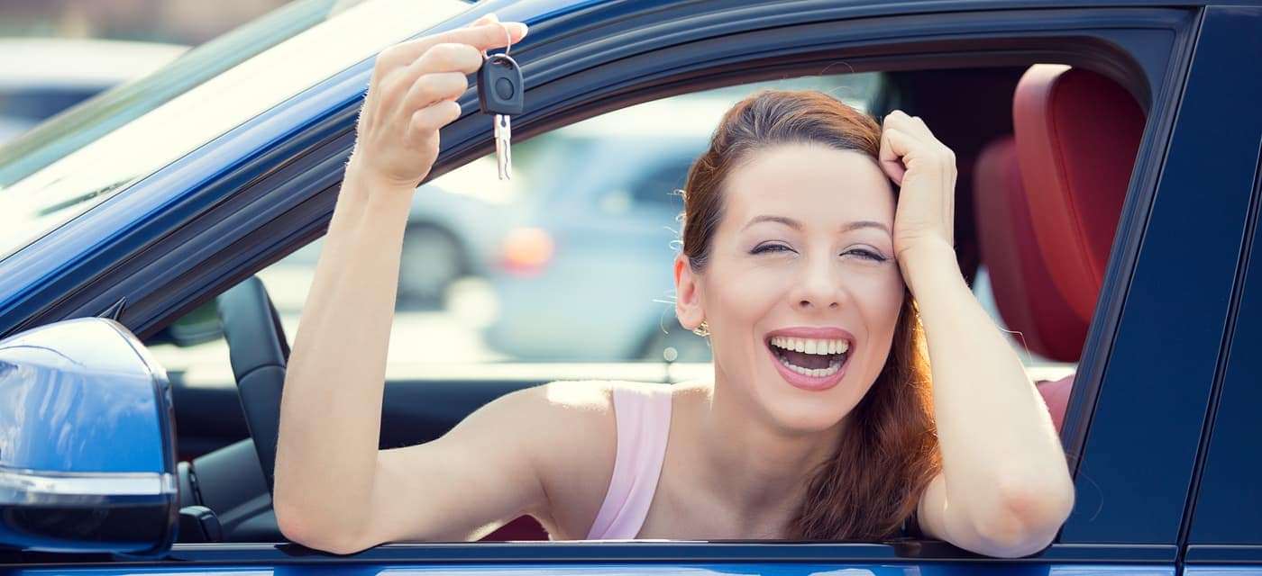 woman relieved with new car with keys in hand