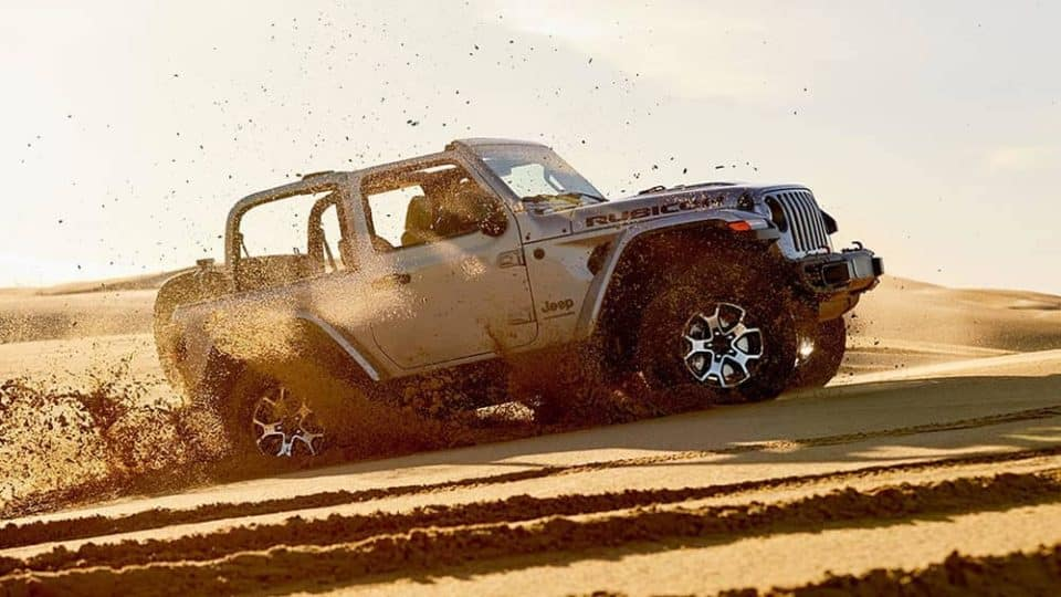 2020 Jeep Wrangler driving off road in a cloud of dust
